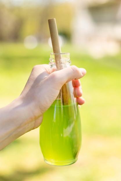 Close-up hand met glazen fles met sap en papier stro Gratis Foto