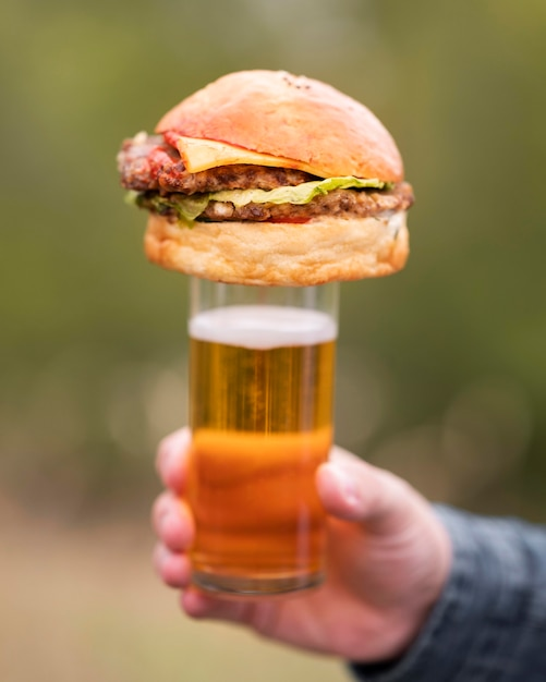 Close-up hand met hamburger bovenop glas Gratis Foto
