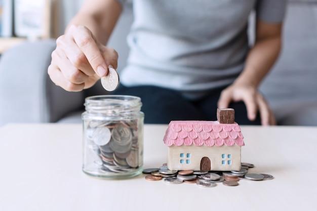 Close-up hand met munt, stapel geld en speelgoed huis op tafel, sparen voor toekomstig concept. Premium Foto