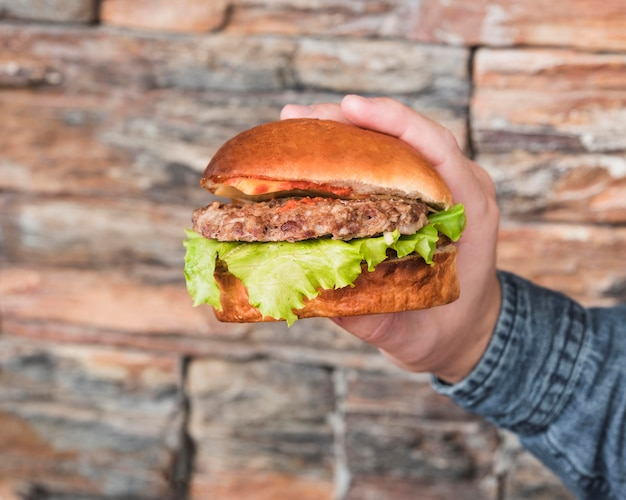 Close-up hand met smakelijke hamburger Gratis Foto