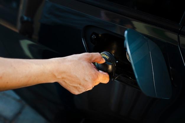 Close-up hand opening autotank Gratis Foto