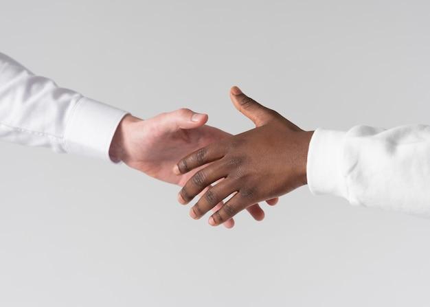 Close-up hand schudden met witte achtergrond Premium Foto