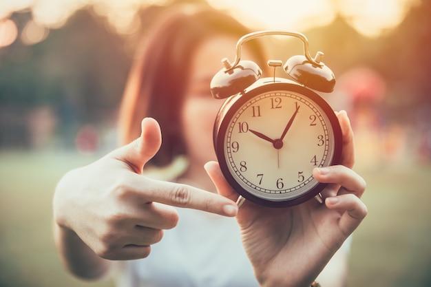 Close-up hand wijzend op kloktijden want het is tijd om een urgent of berichtconcept te doen. Premium Foto