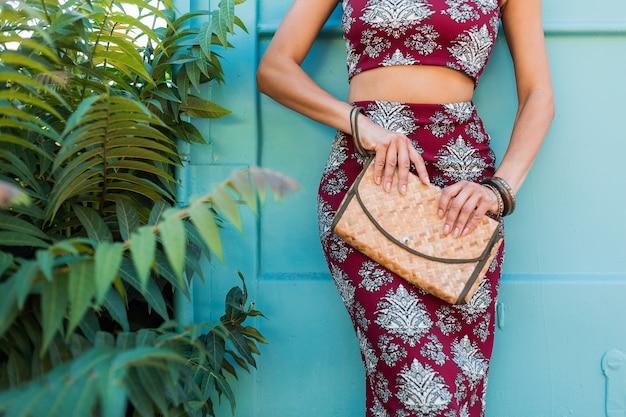 Close-up handen details met stro handtas, stijlvolle mooie vrouw poseren op blauwe muur, gedrukte outfit, zomerstijl, modetrend, top, rok, mager, accessoires, tropische vakantie Gratis Foto