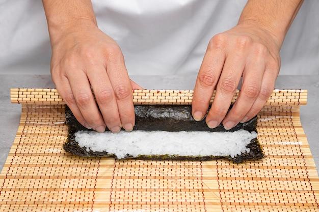 Close-up handen heerlijke sushi voorbereiden Gratis Foto