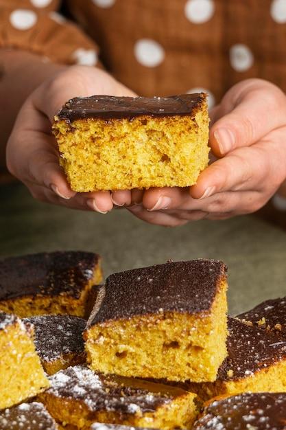 Close-up handen met heerlijke cake Gratis Foto