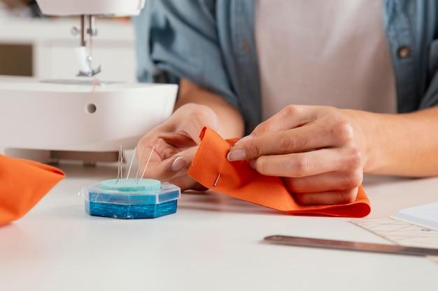 Close-up handen oranje stof naaien Premium Foto