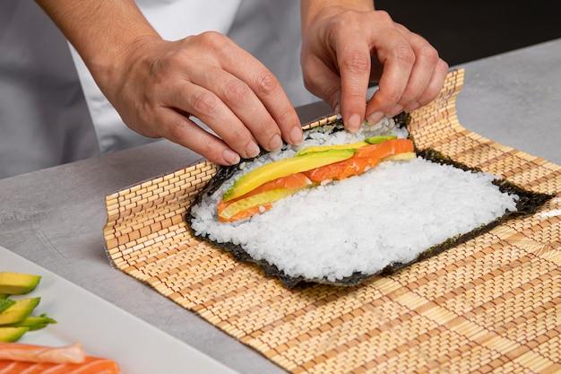 Close-up handen smakelijke sushi voorbereiden Gratis Foto