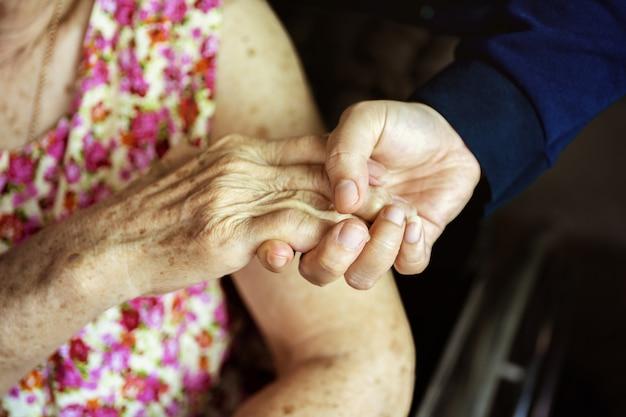 Close-up, handen van een bejaarde die de hand van een jongere vrouw houdt. medisch en gezondheidszorgconcept Premium Foto