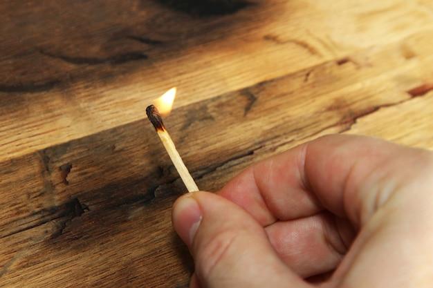 Close-up hoge hoek die van een persoon is ontsproten die een brandende lucifer over een houten oppervlak houdt Gratis Foto