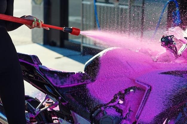 Close-up hogedruk roze schuim wast een motorfiets bij self-carwash. selectieve aandacht. Premium Foto