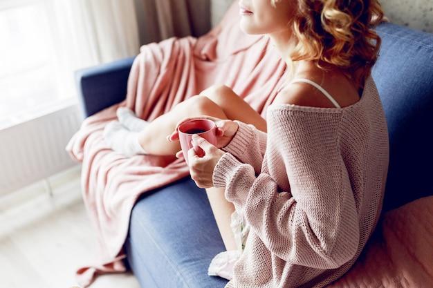 Close-up indoor portret van gracieuze blonde vrouw genieten van geur van cappuccino, dromen en kijken naar het raam. roze gebreide trui dragen. Gratis Foto