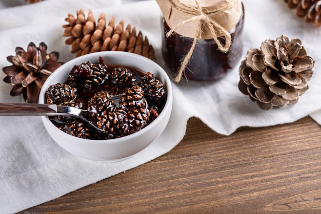 Close-up jam van jonge dennenappels in witte kom met kegels en pot op witte keukenhanddoek op houten tafel Premium Foto