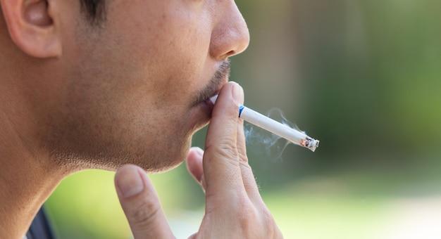 Close-up jonge man het roken van een sigaret Premium Foto