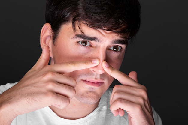 Close-up jonge man neus aanraken Gratis Foto
