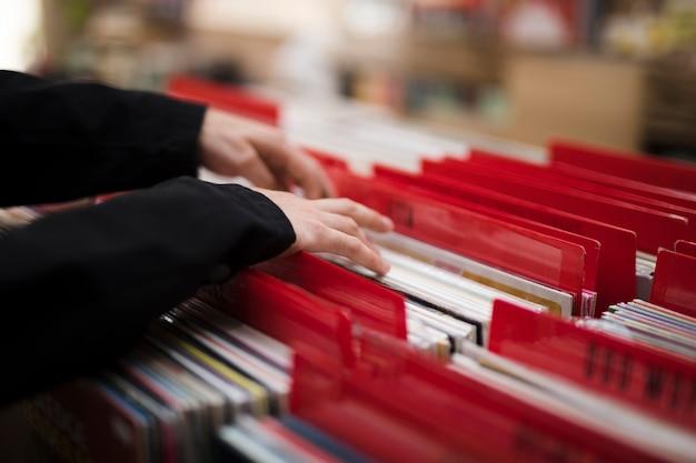 Close-up jonge man op zoek naar vinyl in de winkel Gratis Foto