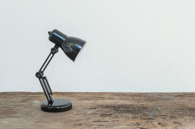 Close-up kleine lamp op houten bureau en de witte geweven achtergrond van de cementmuur met exemplaarruimte Premium Foto