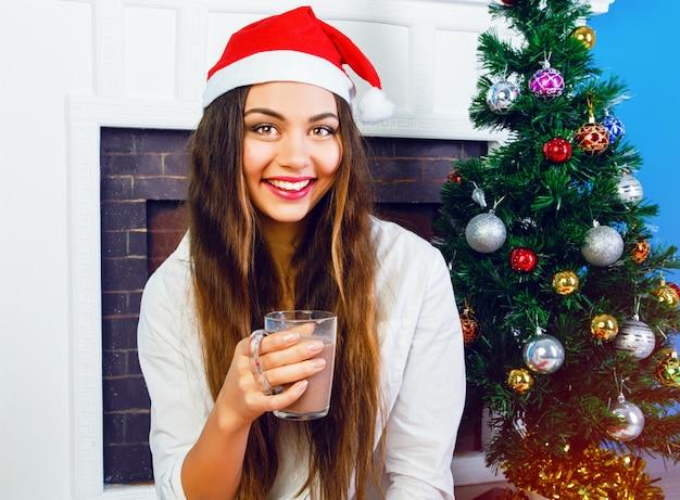 Close-up levensstijl portret van mooie brunette vrouw warme chocolademelk drinken in oudejaarsavond, kerstmuts dragen en zitten in de buurt van open haard en versierde kerstboom. gezellige huiselijke sfeer. Gratis Foto