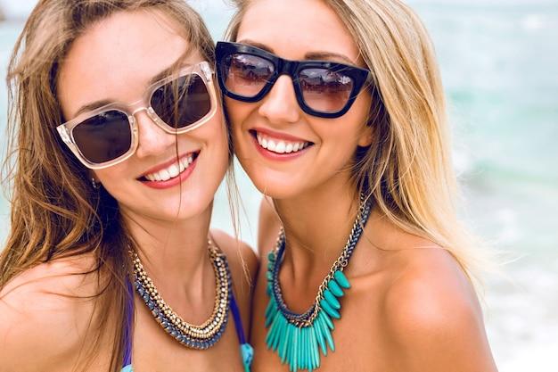 Close-up lifestyle mode portret van twee mooie frisse jonge brunette en blonde beste vrienden meisjes, met vakantie op het strand van het tropische eiland, bikini zonnebril en heldere sieraden dragen. Gratis Foto