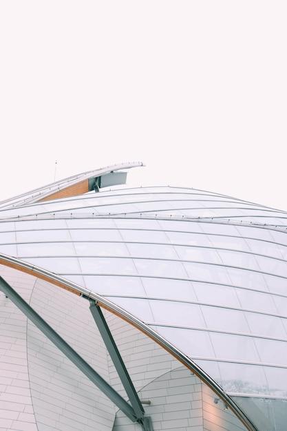 Close-up look van een modern gebouw met witte glazen ramen onder een grijze lucht Gratis Foto