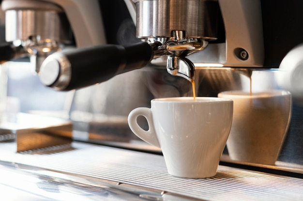 Close-up machine koffie gieten in beker Gratis Foto