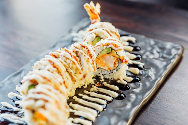 Close-up maki sushi met rijst, garnalen tempura, avocado en kaas in overdekte knapperige tempura bloem. topping met teriyakisaus en mayonaise. Premium Foto