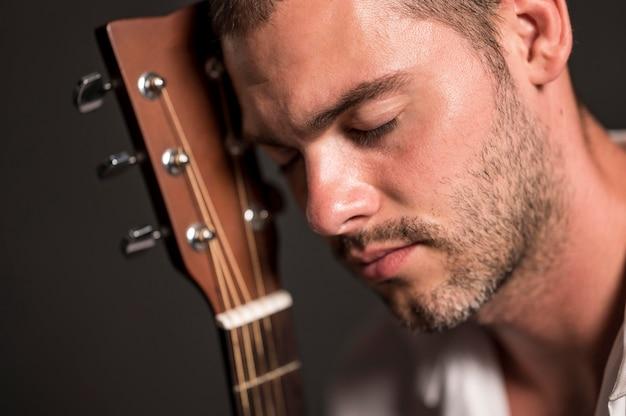 Close-up man met zijn hoofd op gitaar headstock Gratis Foto