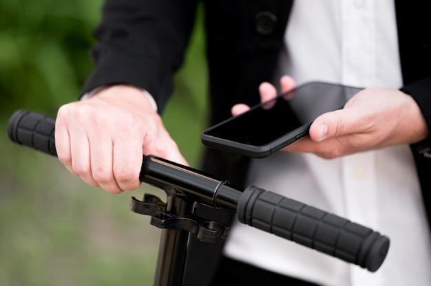 Close-up mannelijke deblokkerende scooter met mobiele telefoon Gratis Foto