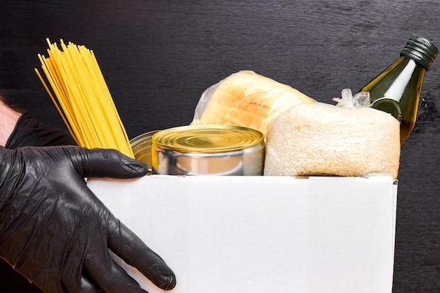 Close-up mans handen in zwarte rubberen handschoenen met een witte doos met pasta, granen en ingeblikt voedsel op een zwarte muur. veiligheid eten bezorgservice. Premium Foto