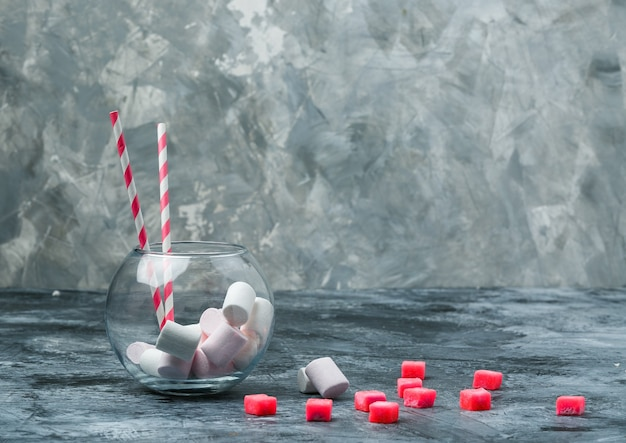 Close-up marshmallows en suikerriet in pot met snoepjes en rood geruit tafelkleed op donkerblauw en grijs marmeren oppervlak. horizontale vrije ruimte voor uw tekst Gratis Foto