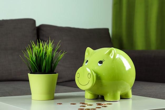 Close-up meisje de hand, gooit een munt in de spaarpot in de vorm van een groen varken Premium Foto