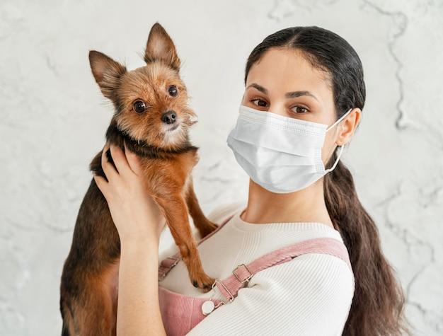 Close-up meisje met de hond van de maskerholding Gratis Foto