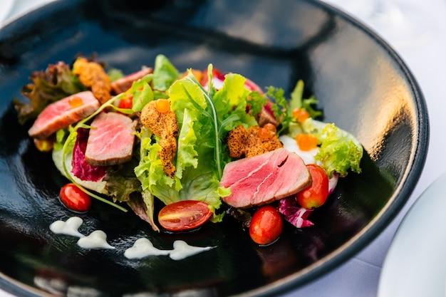 Close-up middelgrote zeldzame tonijnsalade met aangeraakte zee-egels in zwarte plaat. Premium Foto