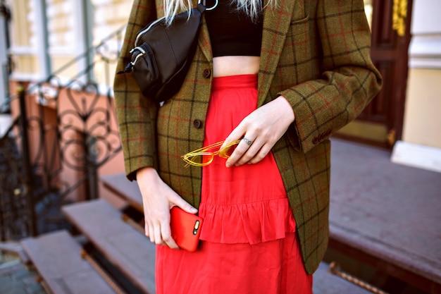 Close-up mode details van vrouw poseren op straat in de buurt van luxewinkel, het dragen van crop top, oversized jas en vrouwelijke rode rok, zonnebril en haar telefoon, moderne zakenvrouw. Gratis Foto