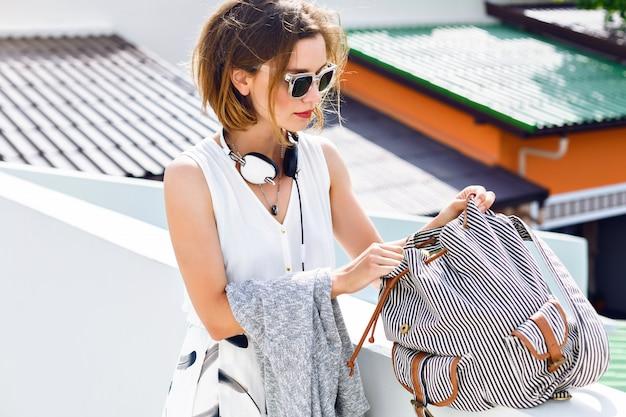 Close-up mode portret van jonge hipster mooie vrouw, iets zoeken in haar rugzak, wandelen en plezier maken op het dak, stijlvolle streetstyle outfit. Gratis Foto