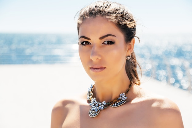 Close-up mode portret van jonge mooie vrouw in stijlvolle grote diamanten halsketting poseren haar zeezijde. lichte, zuivere kleuren. Gratis Foto