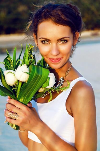 Close-up mode portret van mooie bruid met verse natuurlijke make-up en eenvoudige witte top, poseren met exotische lotus boeket bij zonsondergang op het strand. Gratis Foto