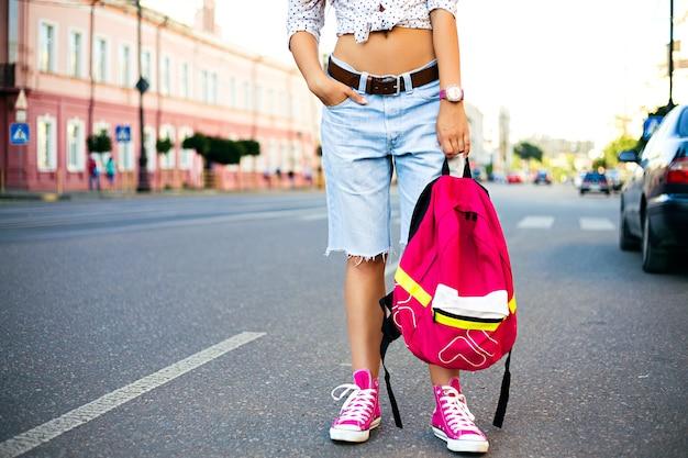 Close-up mode portret van stijlvolle jongedame, alleen reizen met lichte rugzak, casual trendy kleding. hipster meisje lopen op straat, mode details Gratis Foto