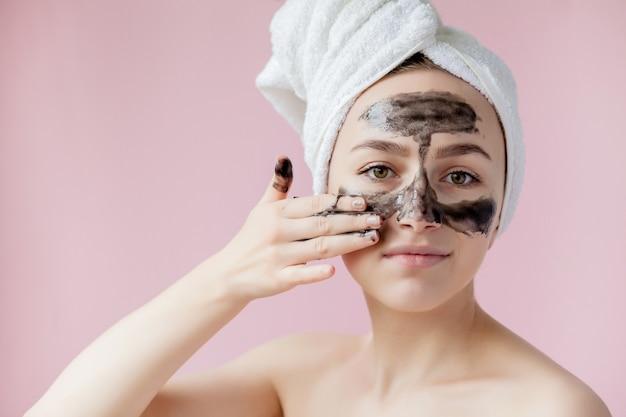 Close-up mooie jonge vrouw met zwarte afpelmasker op huid Premium Foto