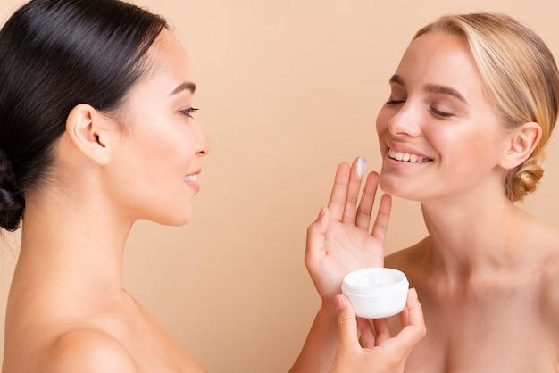 Close-up mooie modellen met gezichtscrème Gratis Foto