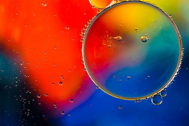 Close-up olieachtige bubbels en druppels in kleurrijke waterige achtergrond Gratis Foto
