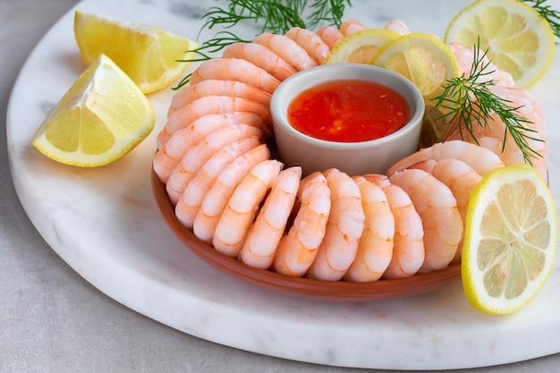 Close-up op garnalenring met zoete spaanse pepersaus op marmeren dienende raad Premium Foto
