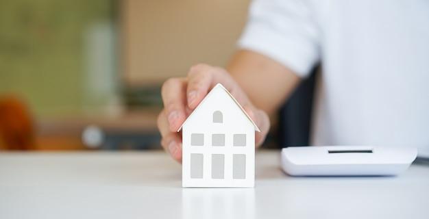 Close-up op man hand aanraken home-model op de tafel voor lening hypotheek en herfinancieren plan Premium Foto