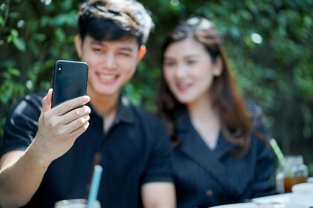 Close-up op man hand met smartphone om foto te nemen (selfie) met vriendinnen Premium Foto