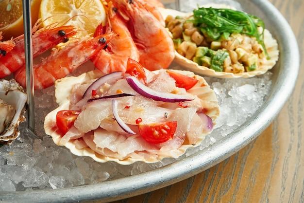 Close-up op tartaar van zeebaars met tomaat en ui in een shell in een plaat op ijs Premium Foto