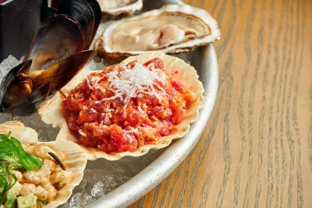 Close-up op. tonijntartaar met tomaat en ui in shell in een plaat op ijs Premium Foto