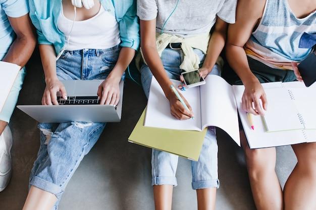 Close-up overhead portret van meisje in blauw shirt en spijkerbroek met laptop op knieën zittend naast universiteitsgenoten. vrouwelijke student die lezing in notitieboekje schrijft en telefoon tussen vrienden gebruikt. Gratis Foto