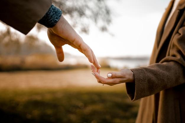 Close-up paar hand in hand buitenshuis Gratis Foto
