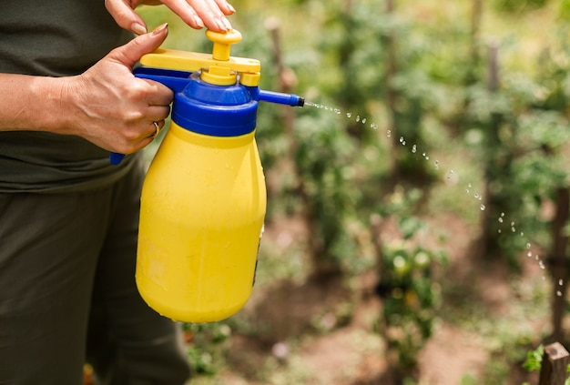Close-up persoon spuiten van pesticiden Gratis Foto
