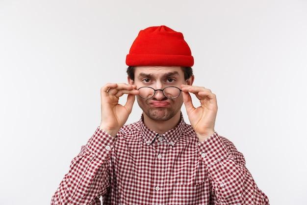 Close-up portret grappige sceptische blanke man in hipster muts, kijk onder het voorhoofd Premium Foto